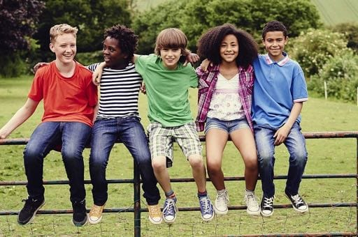 Diverse group of children sitting on a fence