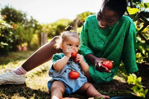 Mother with her child eating apples
