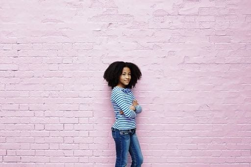 Child against pink brick wall