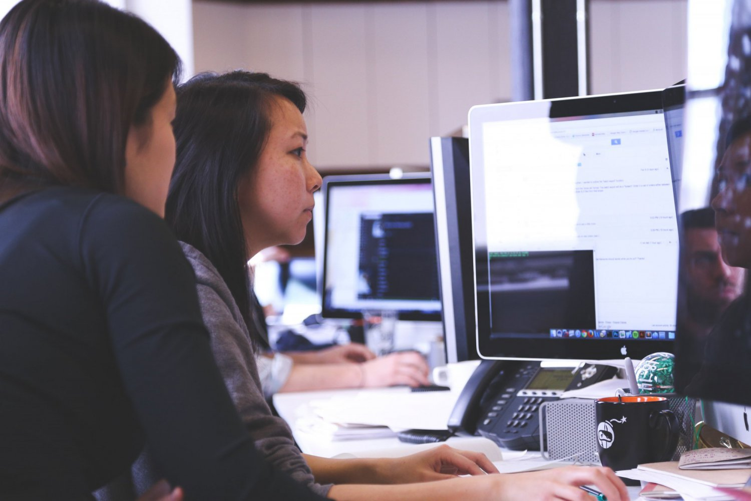 two women sat at a computer screen