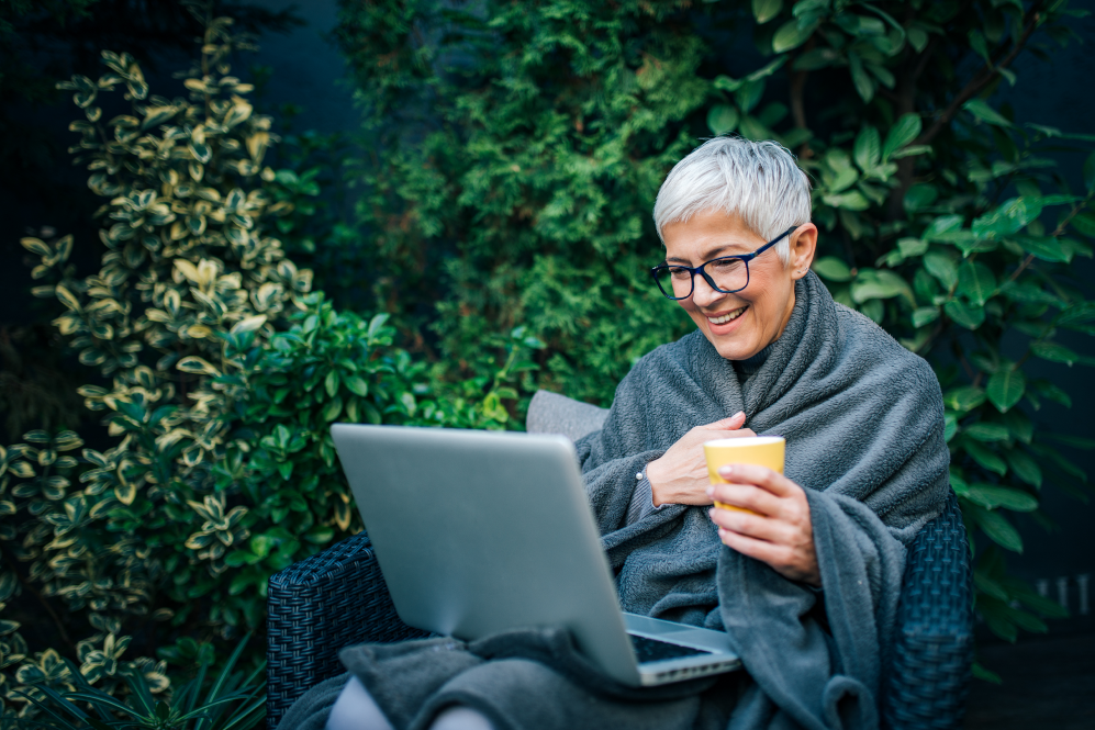An elder woman sitting down smiling in front of a laptop holding a cup of coffee.