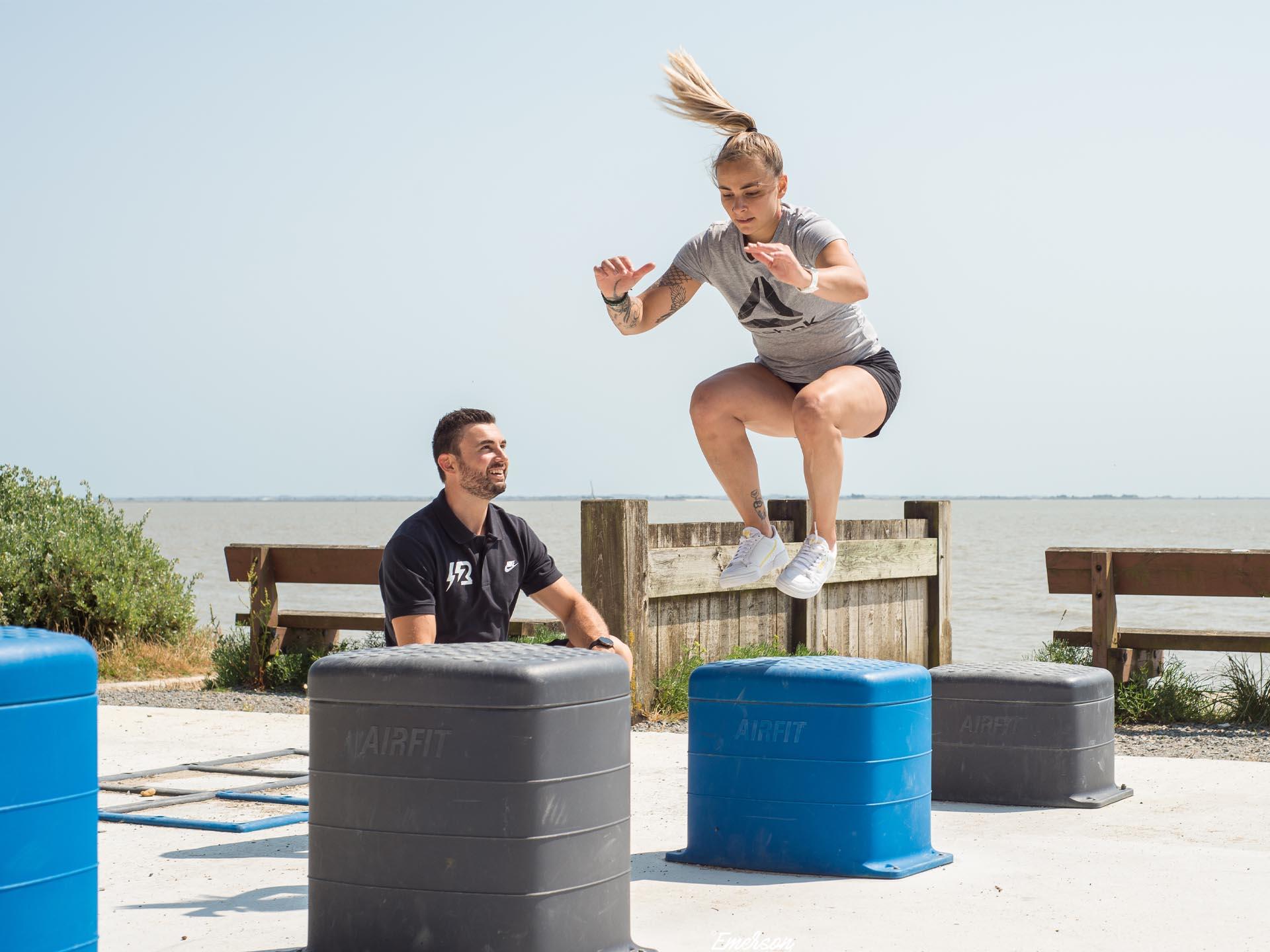 Photo d'une jeune femme accompagnée de son coach sautant sur un Box Jump