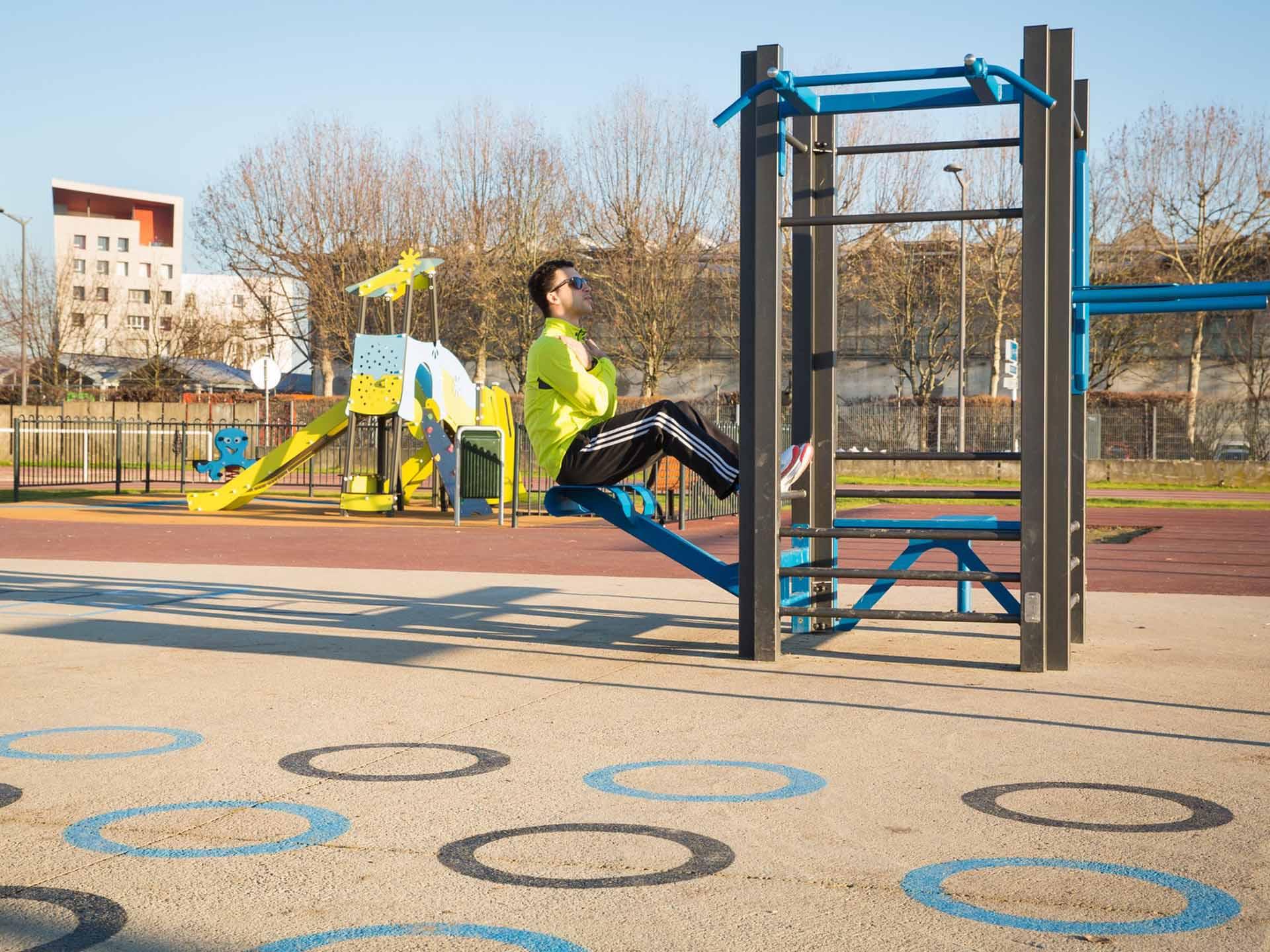 Photo d'un sportif réalisant des abdominaux sur le plateau sportif de Vaulx en Velin