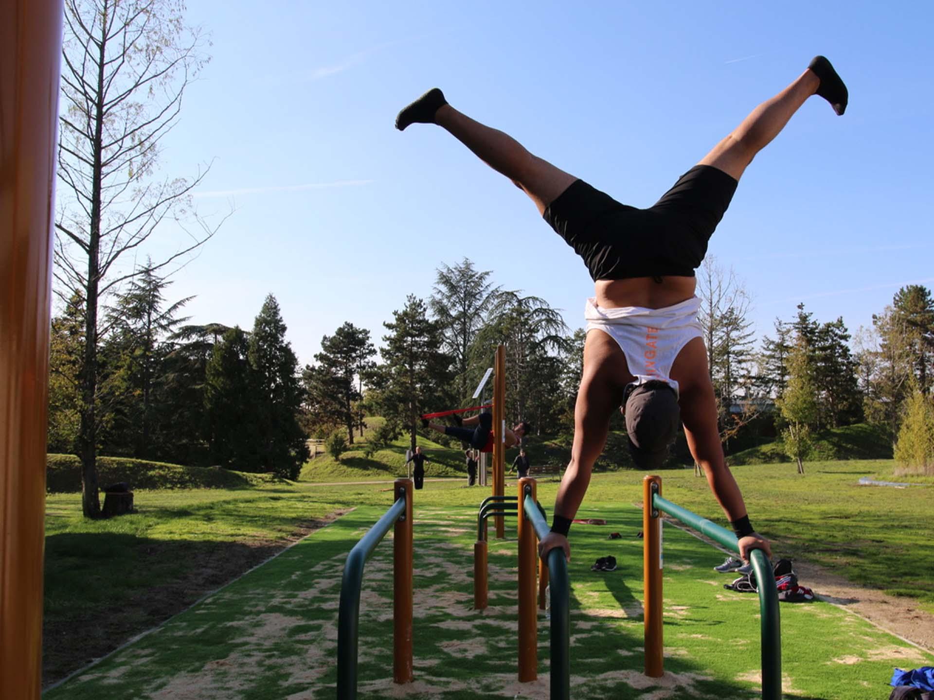 Photo d'un sportif aguerri réalisant une figure sur les barres parallèles à Issoudun