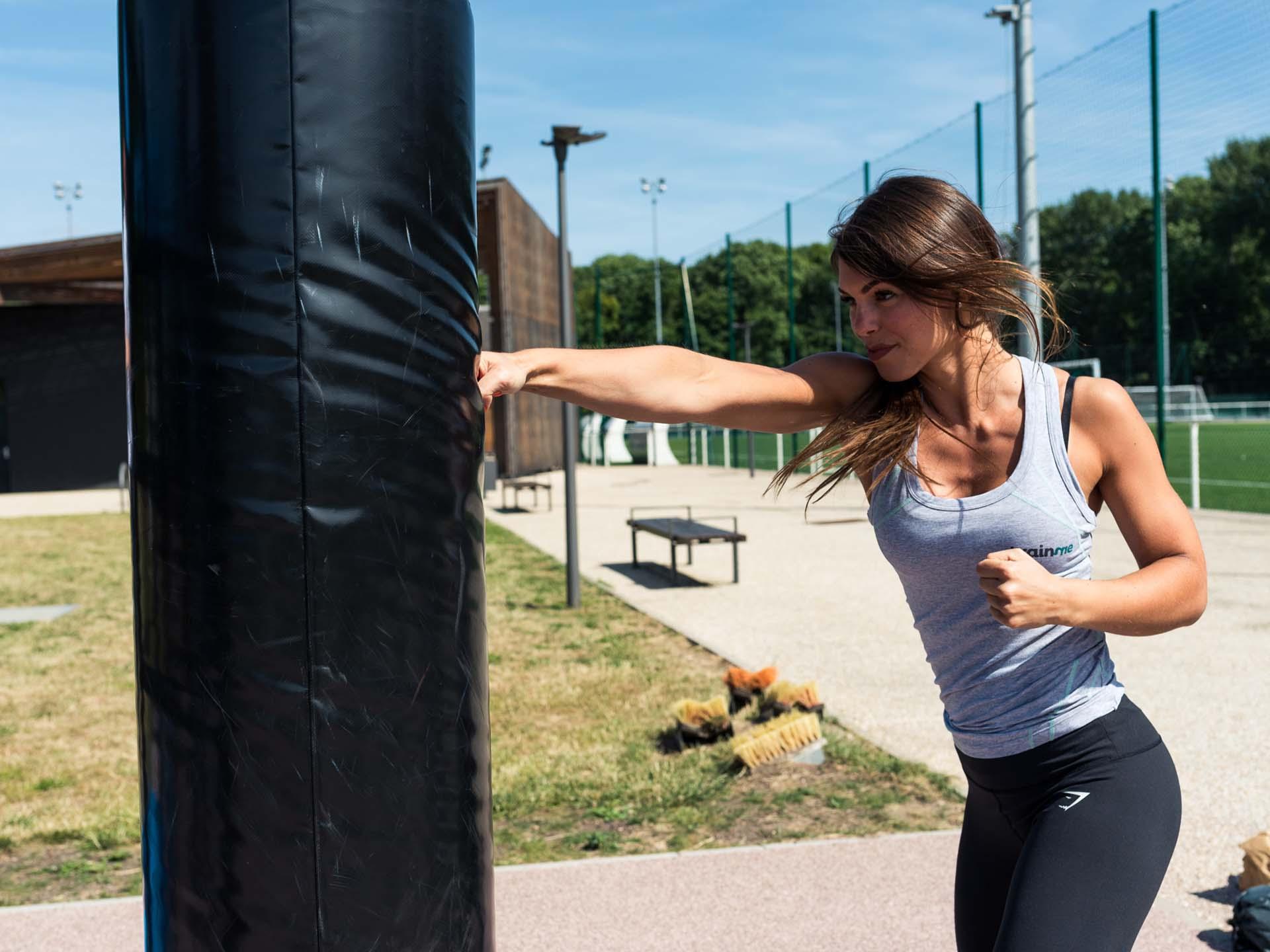 Photo d'une femme frappant dans un sac de boxe AirFit en extérieur