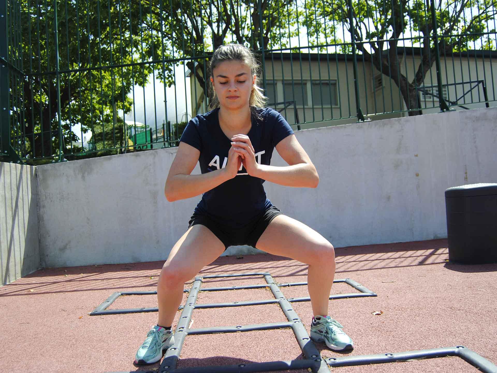 Photo d'une sportive faisant un squat sur l'échelle de rythme du plateau sportif de Meudon