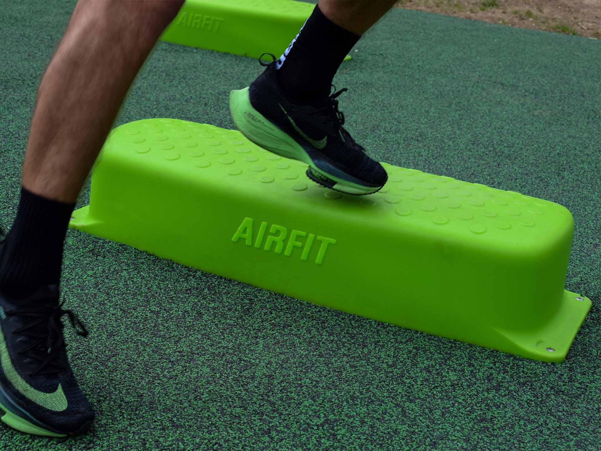 Photo du bas du corps d'un sportif en train de sauter sur un step vert AirFit