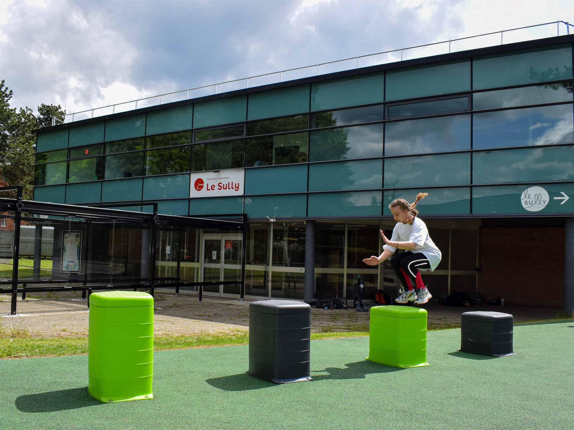 Photo d'une étudiante sautant sur des plints face au restaurant universitaire du CROUS de la cité universitaire de Lille