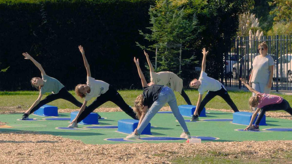 Photo d'un groupe d'enfants en train de faire une séance de sport ensemble face à la borne tactile de l'Arena AirFit de Mandelieu