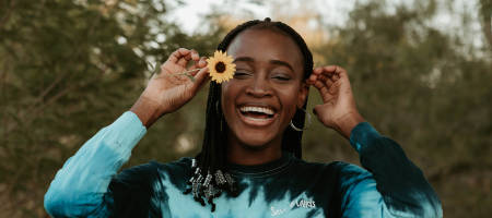 A black girl holding a flower in her hand and smiling big
