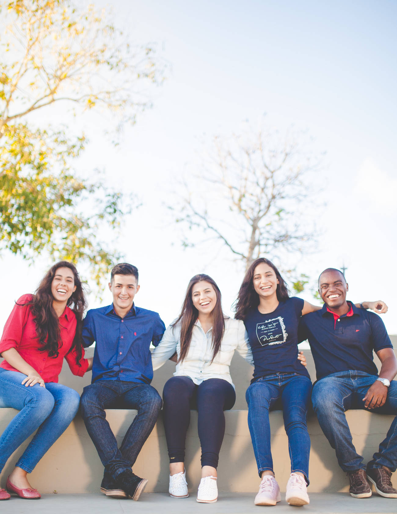 A group of happy young people sitting down posing for the camera