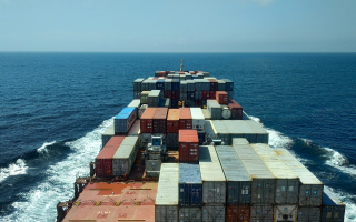 A freighter filled with containers sailing on the ocean.