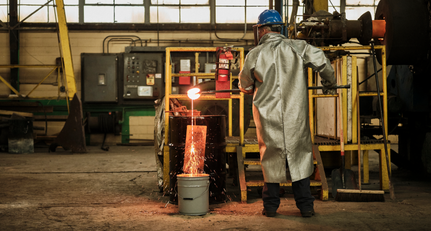 Candid portrait of a Sabin employee in protective heat gear working with molten metal.