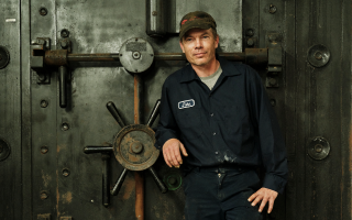 A heroic portrait of a Sabin employee standing in front a safe.