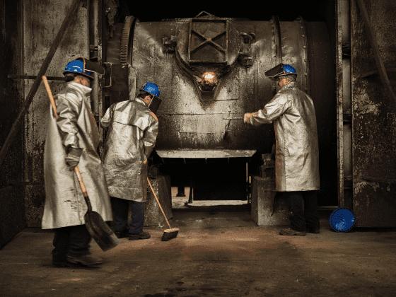 Three Sabin employees in protective heat gear working near a blast furnace.