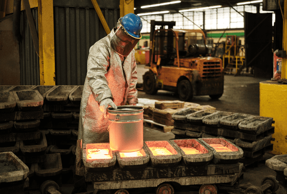 A candid shot of a Sabin employee in protective heat gear working with molten metal.