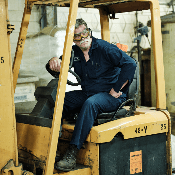 A heroic portrait of a Sabin employee operating a forklift.