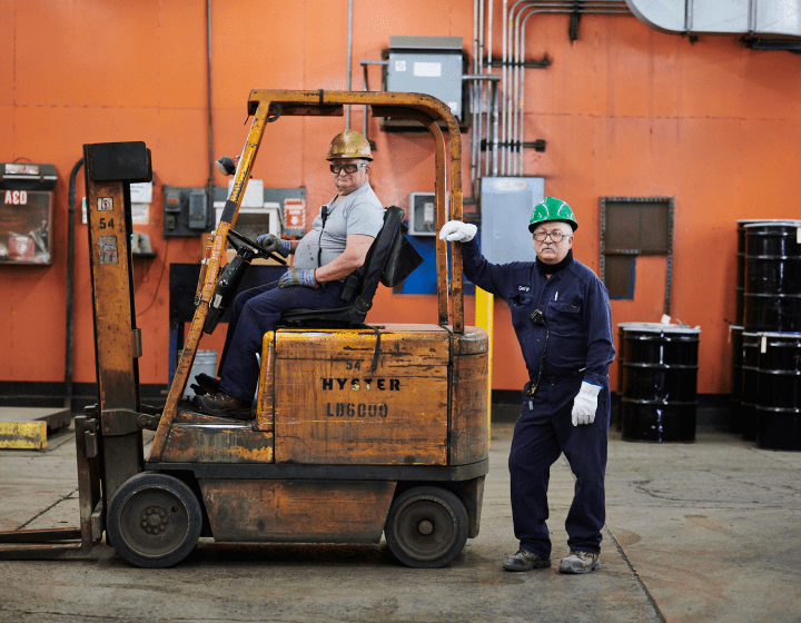 A heroic portrait of two Sabin employees standing near a forklift.