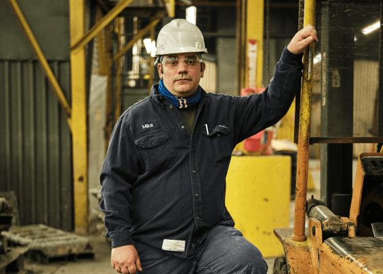 A heroic portrait of a Sabin employee with a hard hat standing by a forklift.