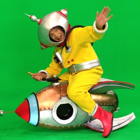 Les Bubb dressed as a spaceman riding a rocket in front of a greenscreen backdrop