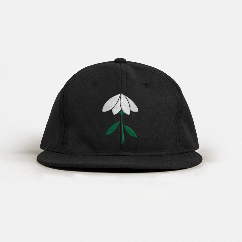 A black baseball hat with a flower embroidered on the front.