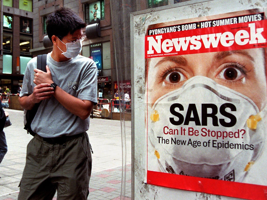 """Man looking at a sign that reads """"SARS, Can it be stopped?"""" during the 2003 epidemic outbreak"""