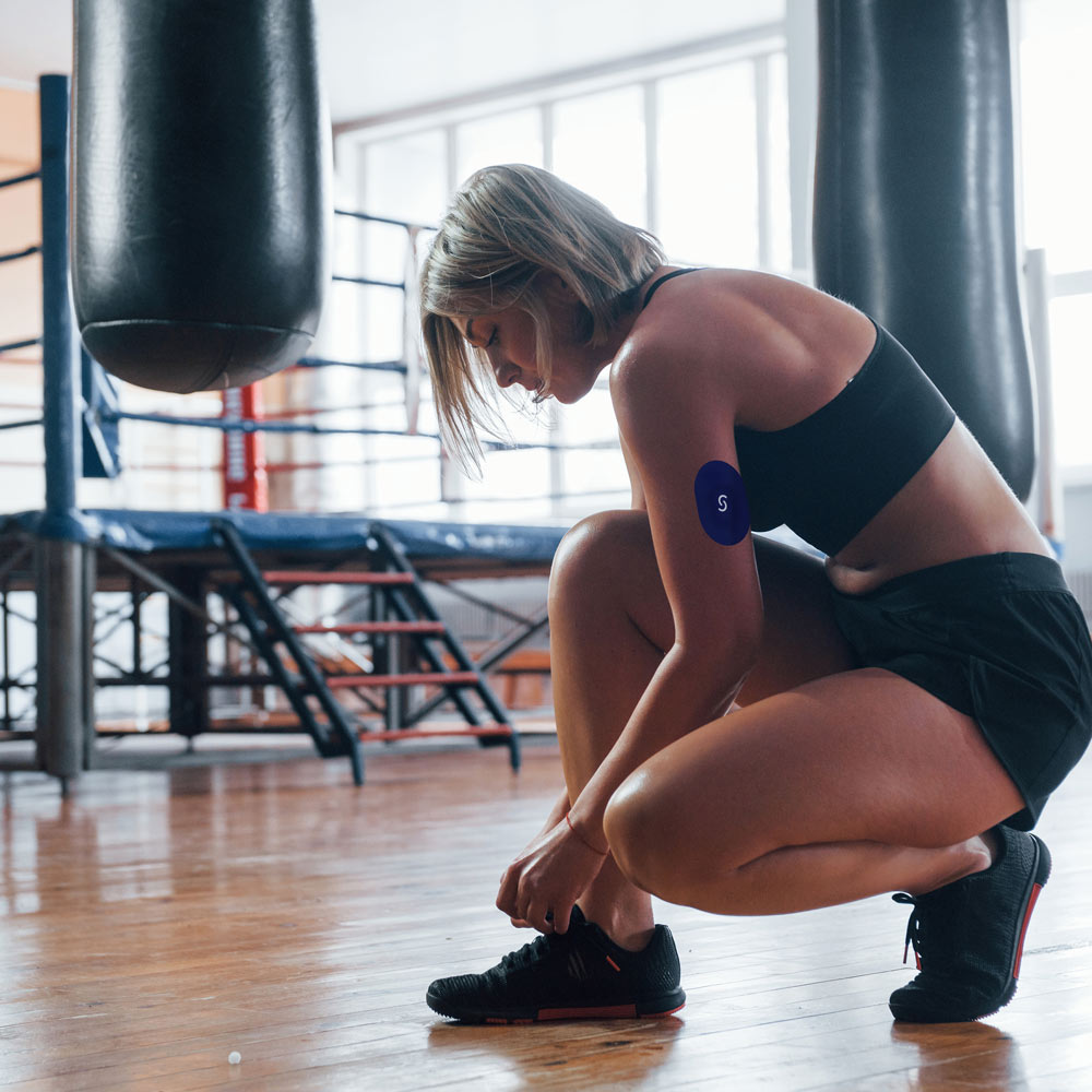 An older white woman crouching down, tying her shoe. She's in a gym and is wearing a grey sports bra and black shorts, and has a CGM and a Signos sports cover on the tricep of her left arm.