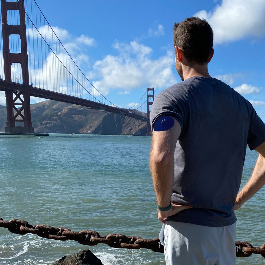 A white man wearing a continuous glucose monitor with a blue Signos sport cover on top on his left arm. His back is facing the camera and he's look at the Golden Gate Bridge.