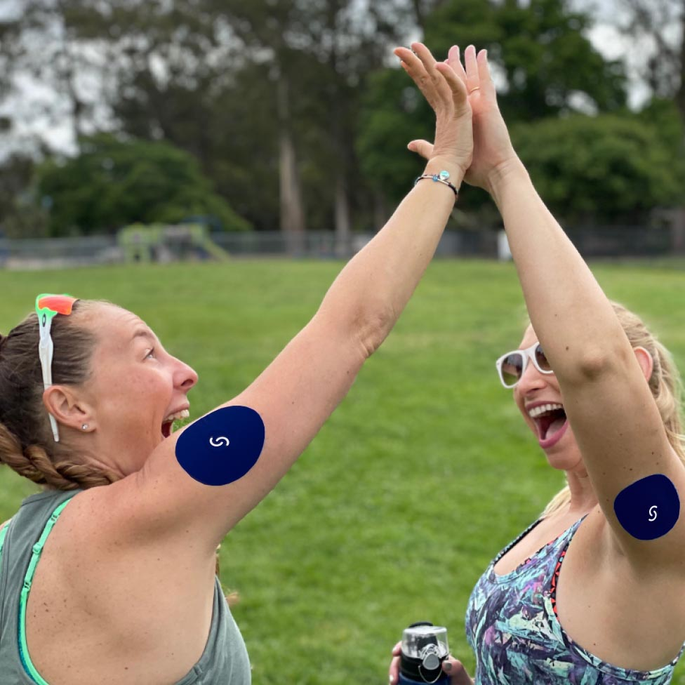 Two white women giving each other a high-five. They are both wearing CGMs with the Signos sports cover on their arms.