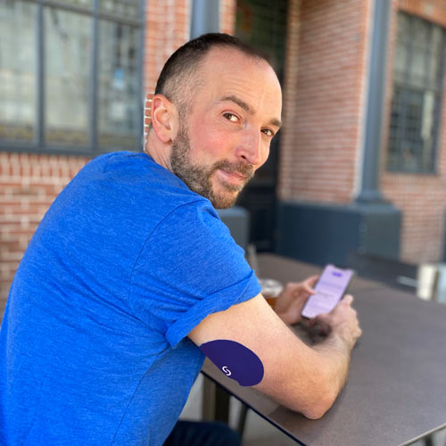 A white man with a beard is sitting at a table with an Android phone in his hands. He's wearing a blue shirt and wearing a CGM with Signos sports cover on his right arm.