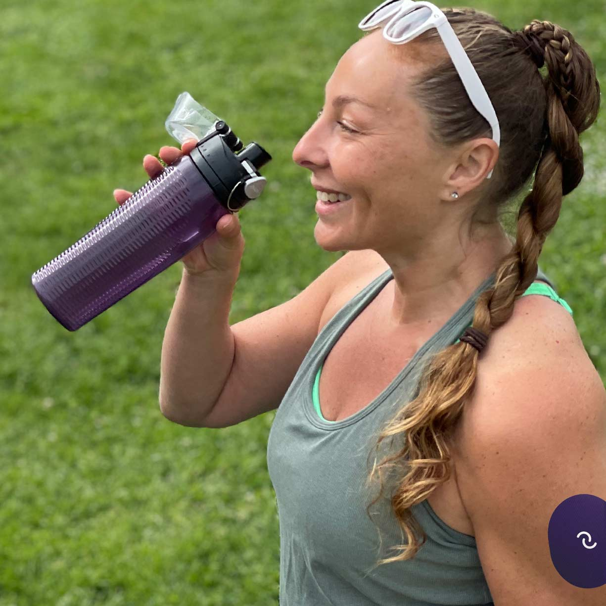 A white woman with a blond braid standing in a park. She's smiling and about to drink water from a reusable water bottle.