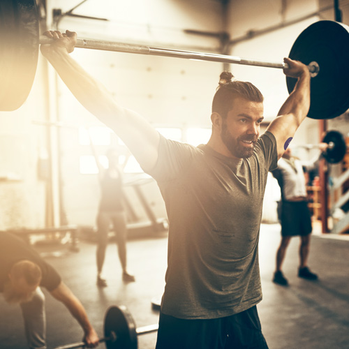 A brown-haired man with a beard is wearing a grey shirt and black shorts and a CGM with a Signos sports cover on his arm. He's lifting a barbell over his head in a gym.