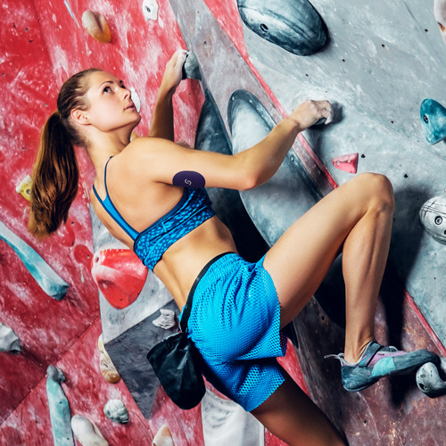 A white woman with brown hair in a ponytail is wearing a blue sports bra and blue shorts. She's doing indoor rock climbing and is wearing a CGM with a Signos sports cover on her right arm.