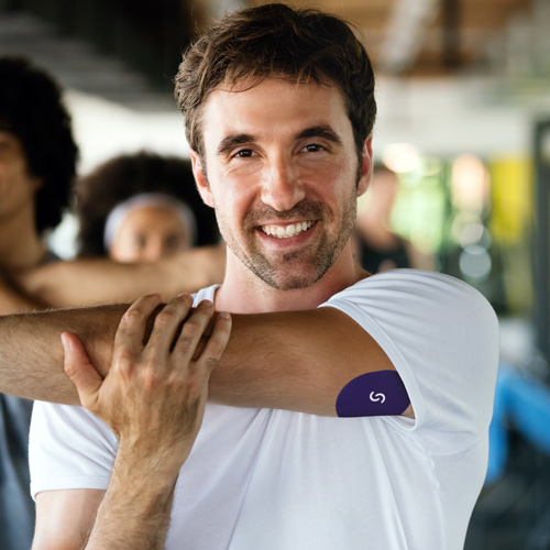 A white man with brown hair is stretching his arm across his chest in a group exercise class. He's wearing a white T-shirt and a CGM with a Signos sports cover on his left arm.