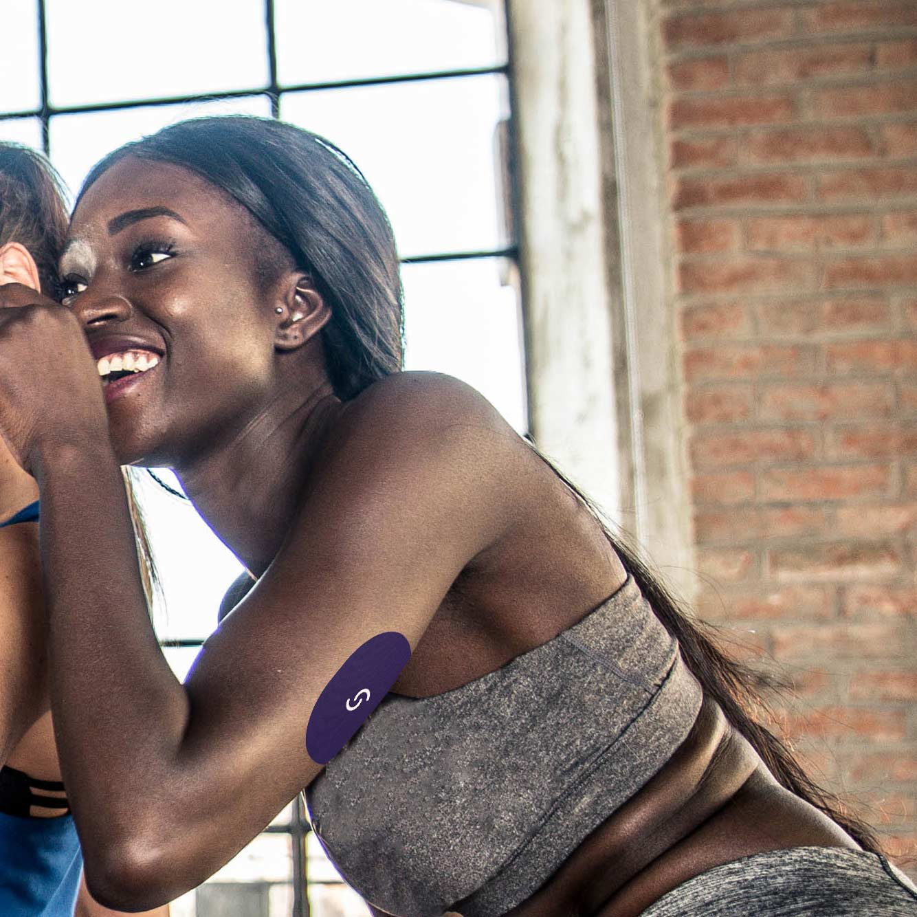 A black woman is wearing a grey sports bra and a CGM with a Signos sports cover on her left arm. She's smiling and squatting with her arms bent.