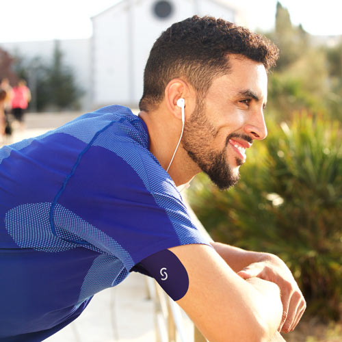 A Hispanic man with a beard wearing a blue shirt and ear buds has a CGM with a Signos sports cover on his arm.