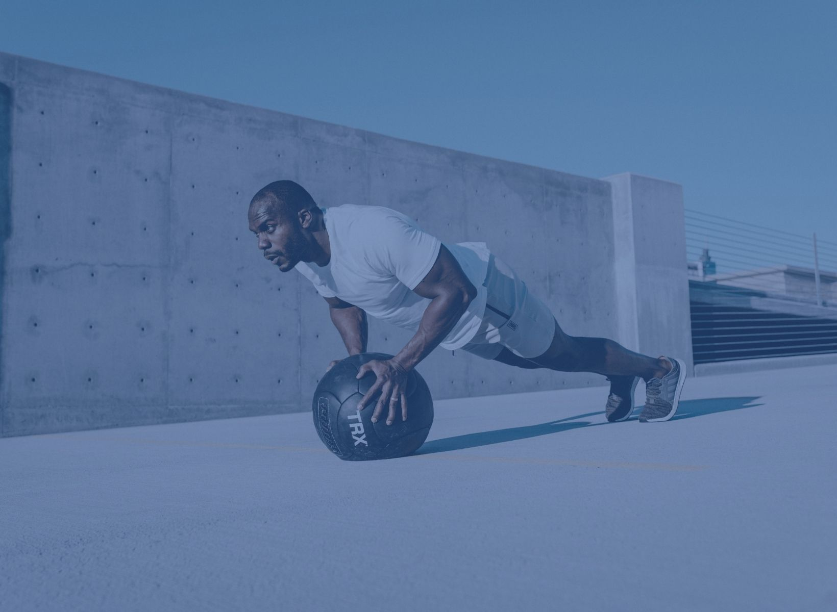 man doing a push-up on a medicine ball. He's exercising to lower blood sugar.