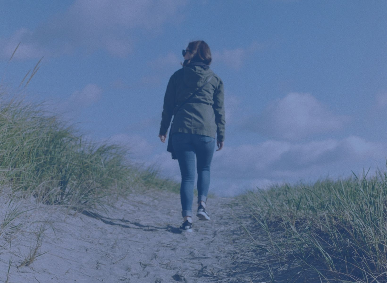 Woman walking away from the camera on a dirt path