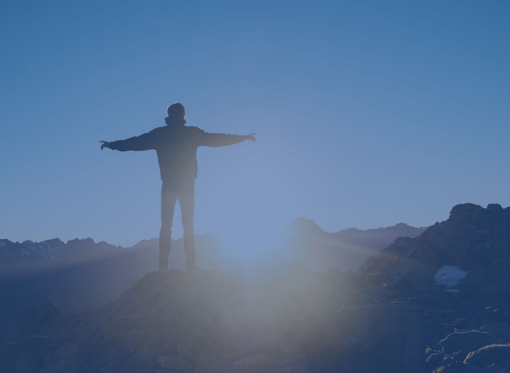 man standing on a hilltop with his arms outstretched, looking at the sunrise