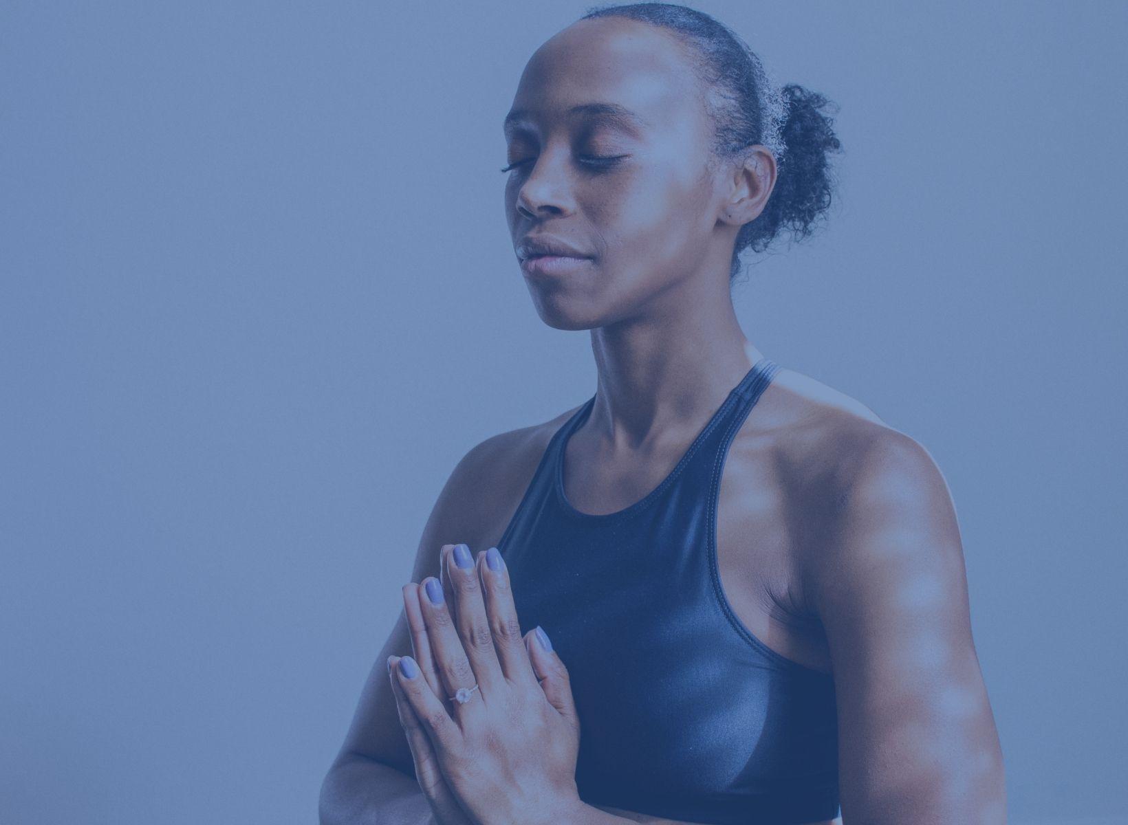 A black woman meditating with her eyes closed and her hands in prayer position in front of her chest
