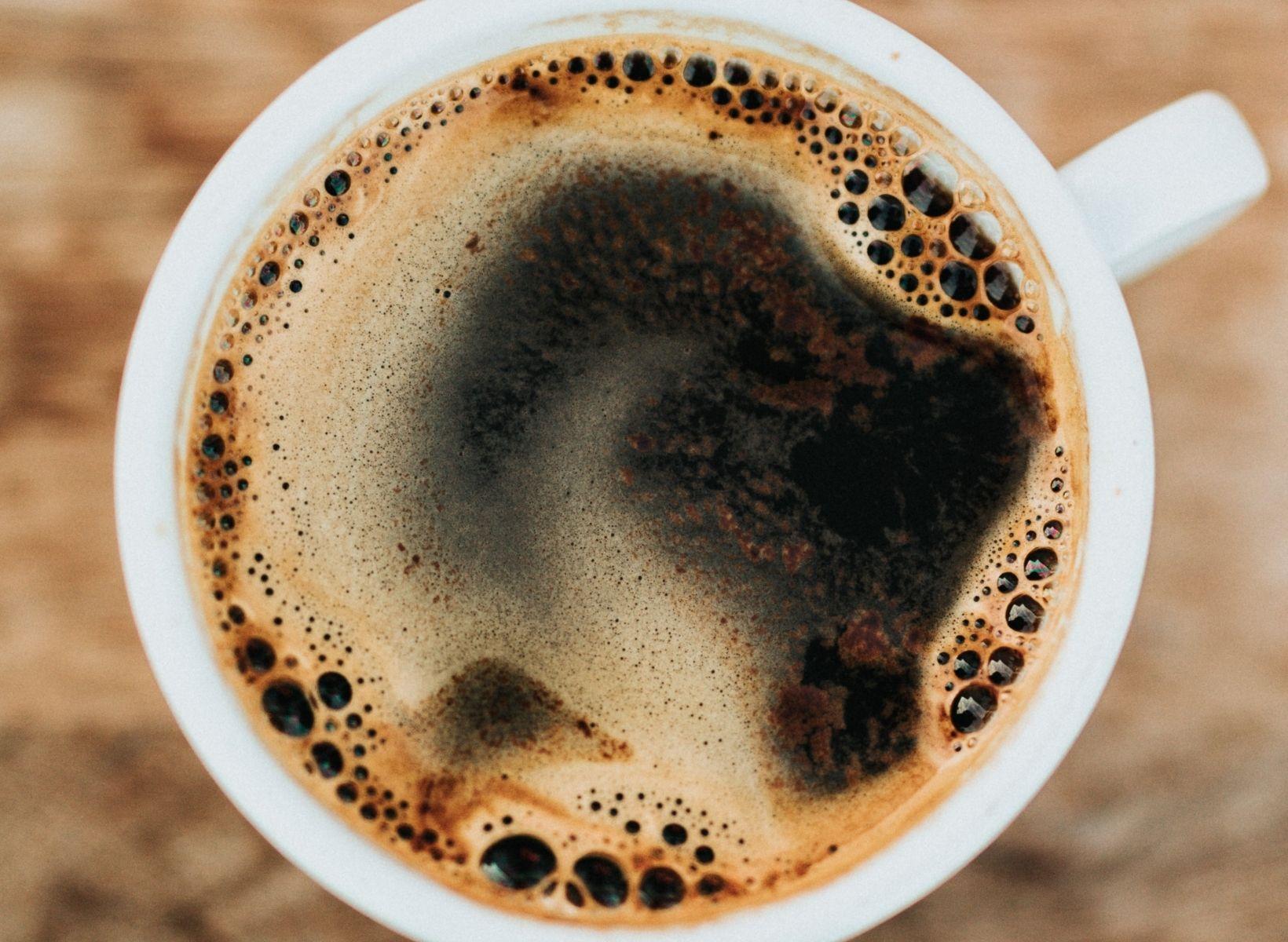 A close up overhead shot of a white mug with black coffee
