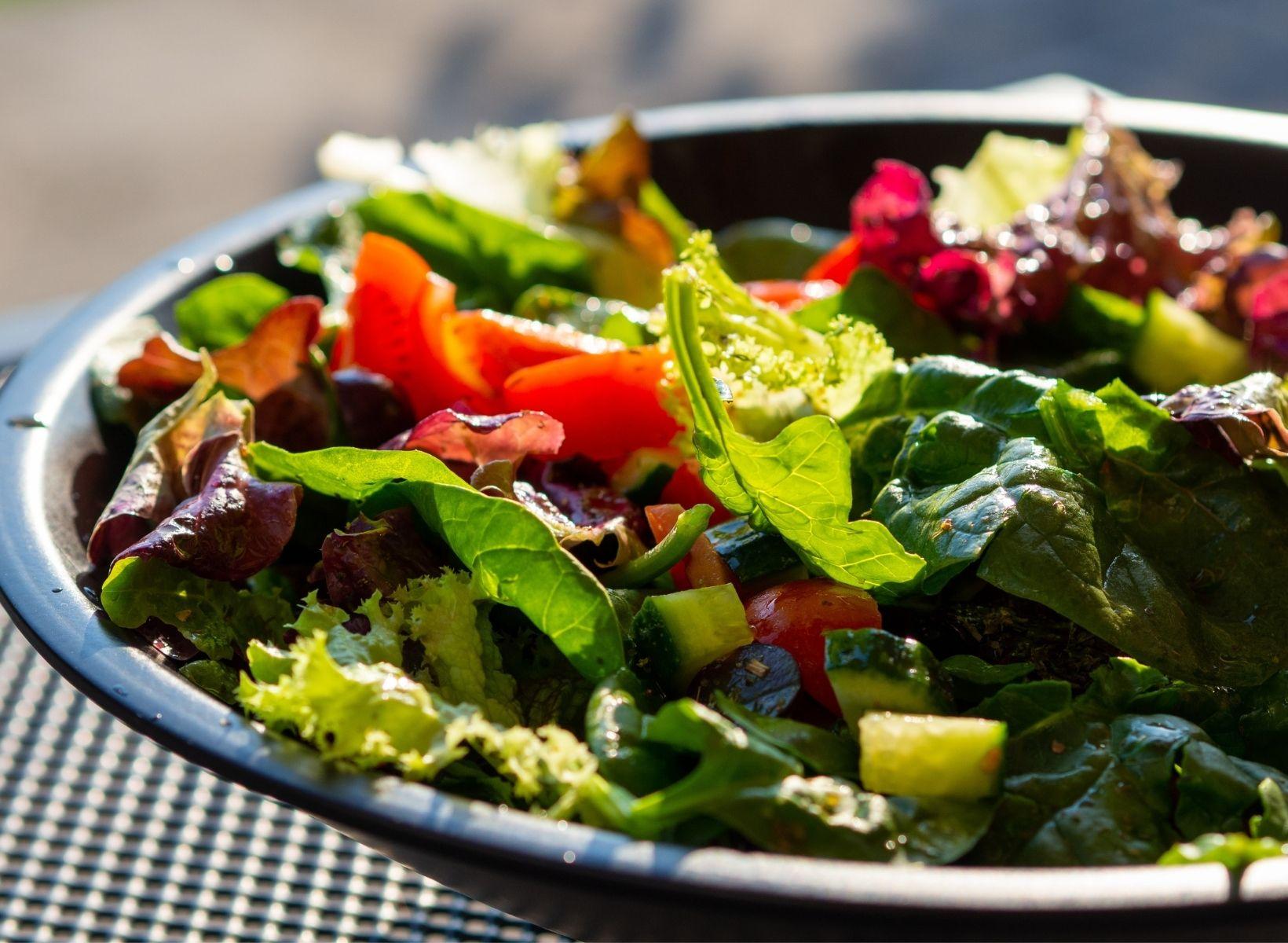 A closeup shot of a black plate piled with Italian chicken mason jar salad