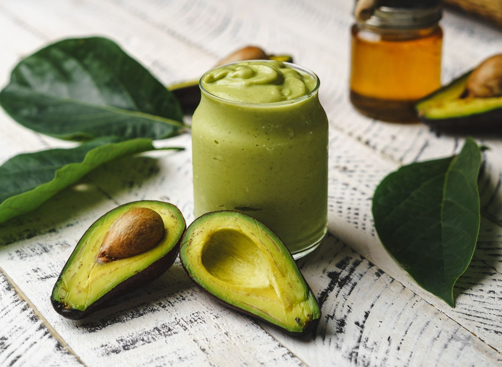 Avocado Cilantro Lime Dressing in a glass jar with green leaves and a ripe avocado cut in half around the jar