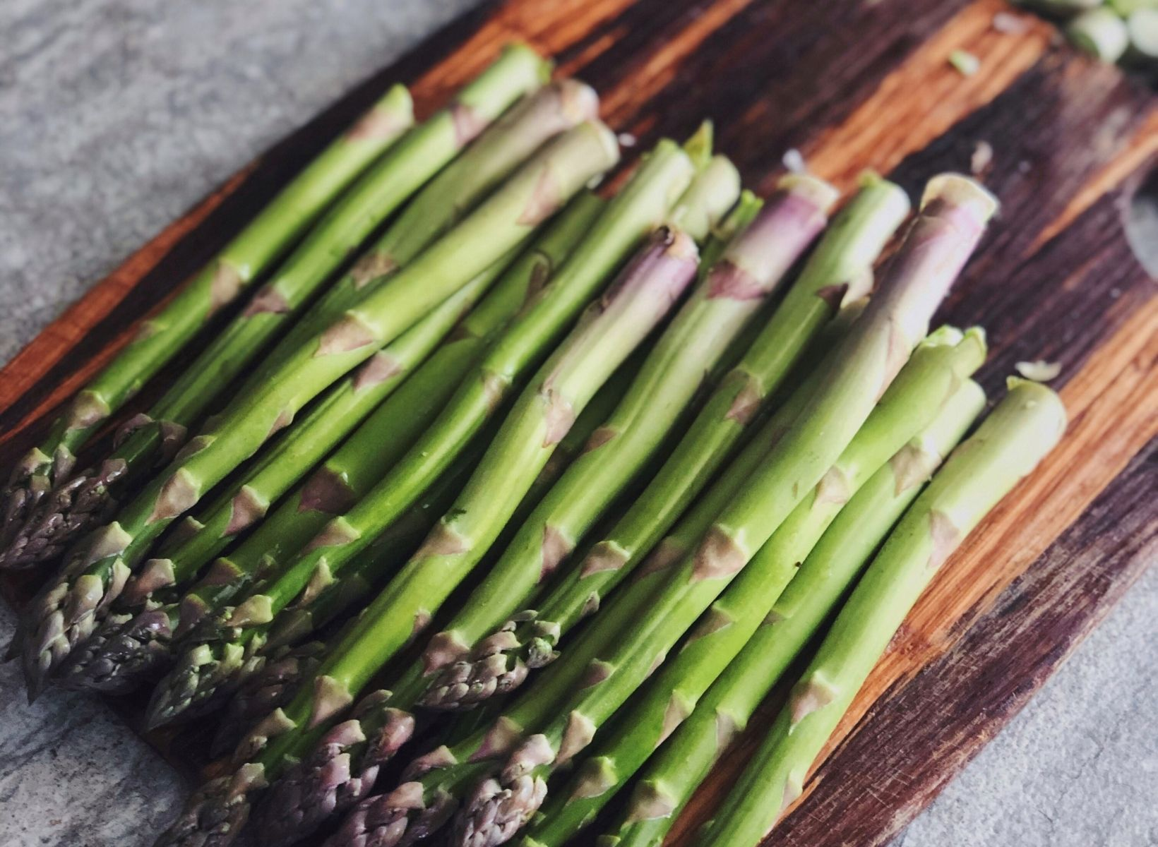 Asparagus spears, a prebiotic food, on a wood cutting board with a knife next to them