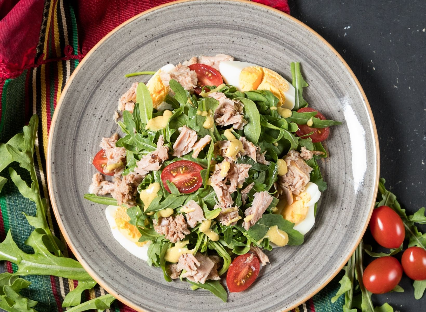 close up of a white plate with a salad made of arugula, lettuce, cherry tomatoes, tuna, and hard boiled eggs