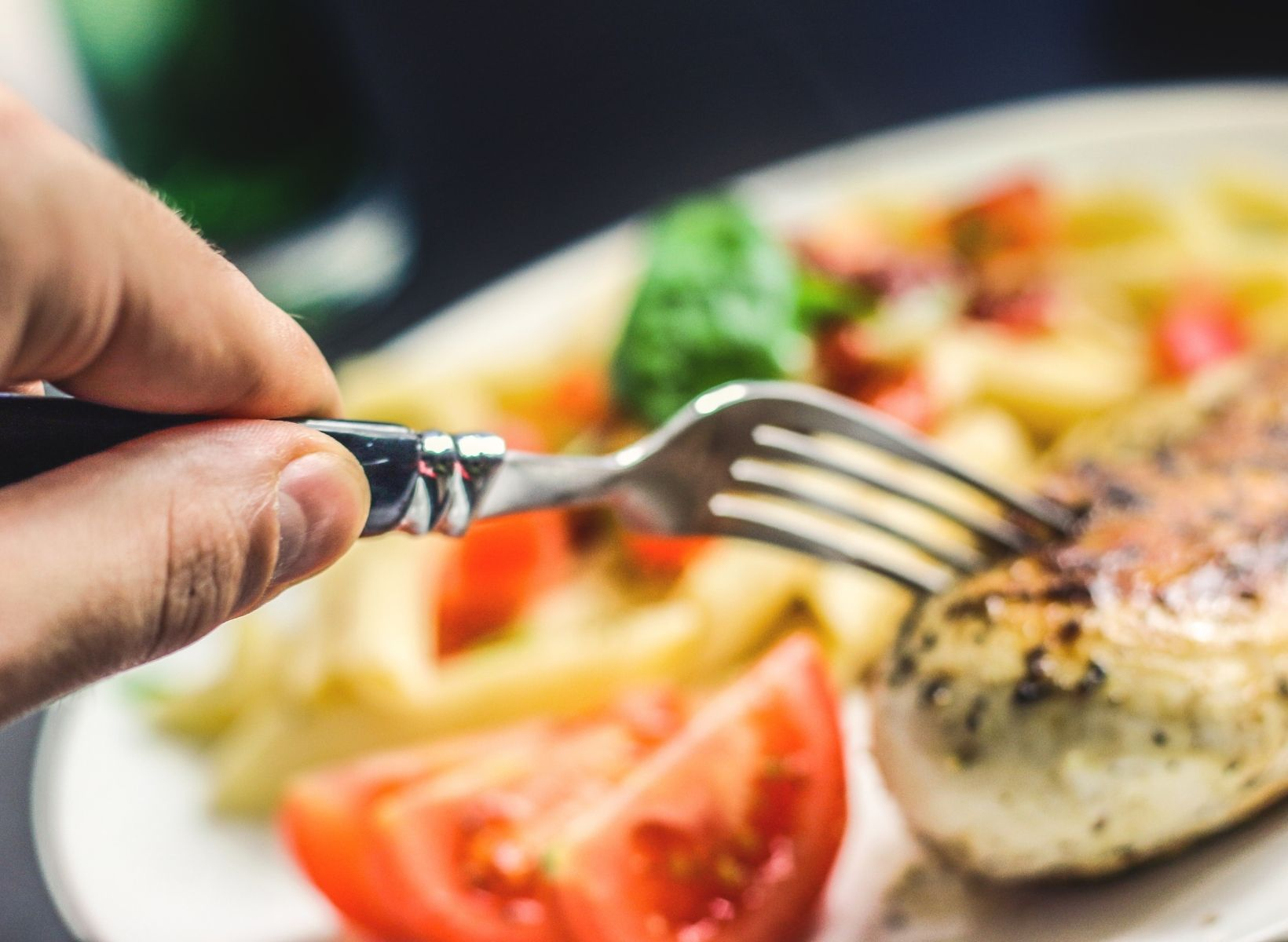 A hand holding a fork poking a cooked chicken breast on a white plate with a tomato slice and blurred vegetables