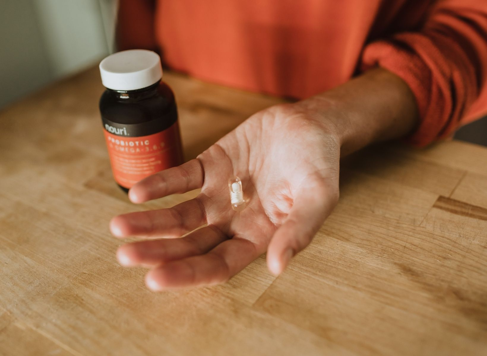 A close up shot of a hand holding a probiotic pill