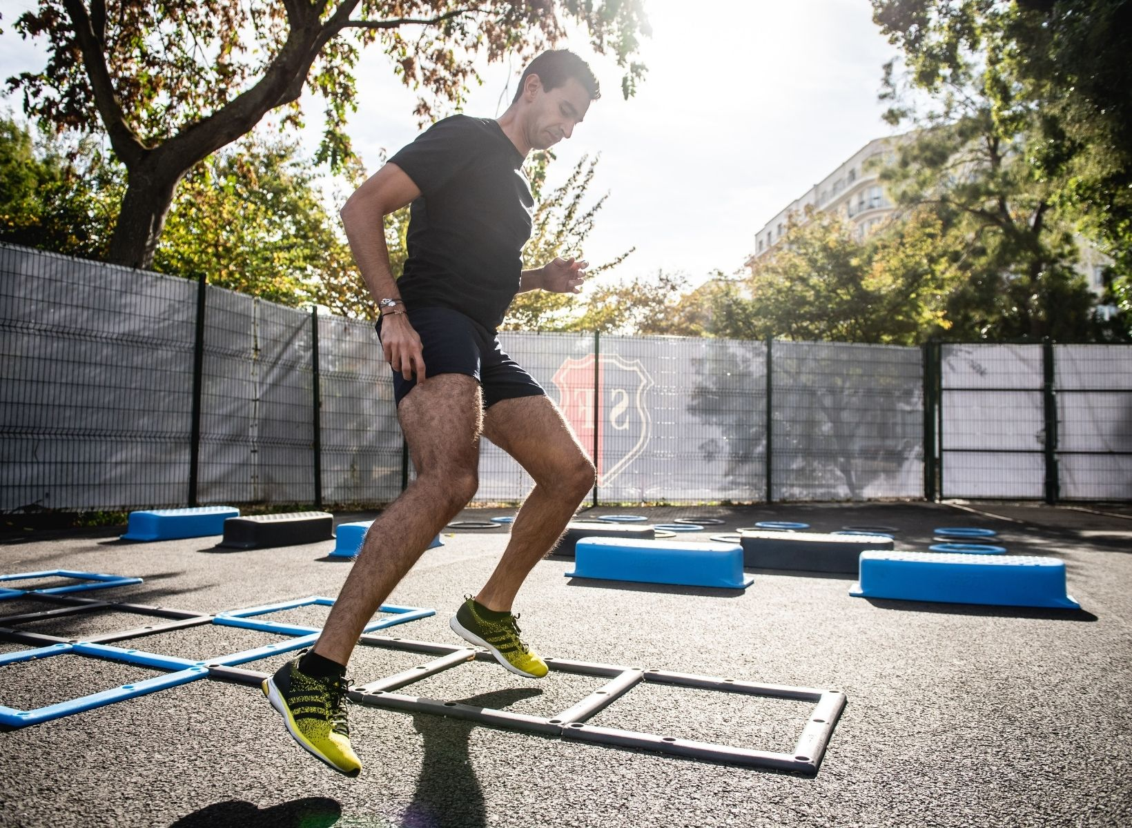 A man outside doing agility drills on a ladder
