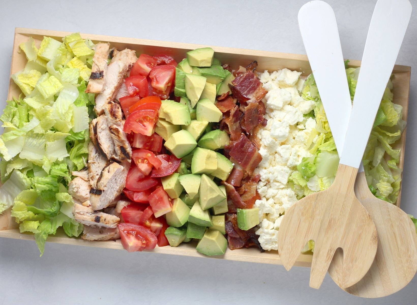Cobb salad on a wooden serving dish with salad serving spoons on the side