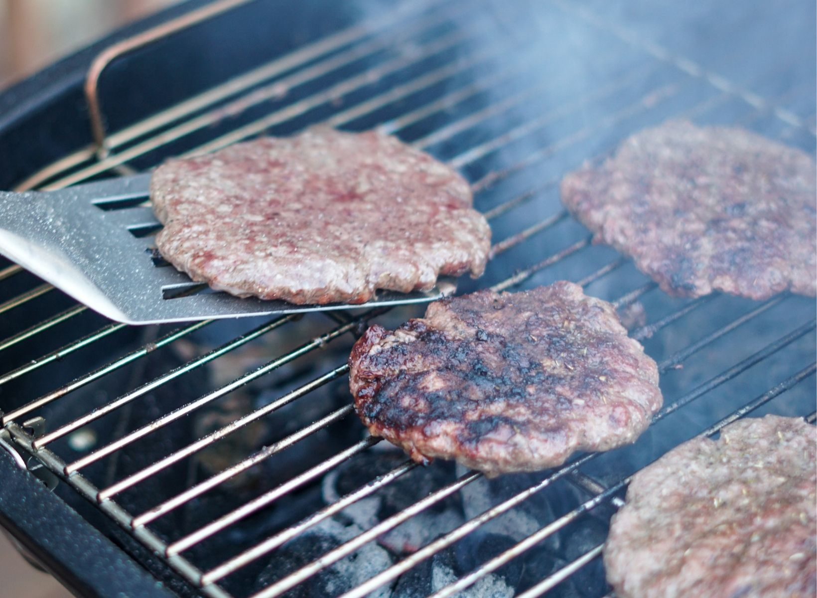 Close up shot of a burger on a spatula. Other burger patties are cooking on the grill grates.